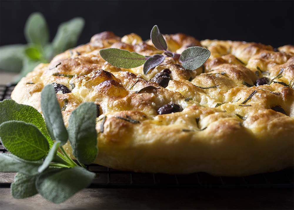 Side view of a browned and crispy loaf of olive focaccia.