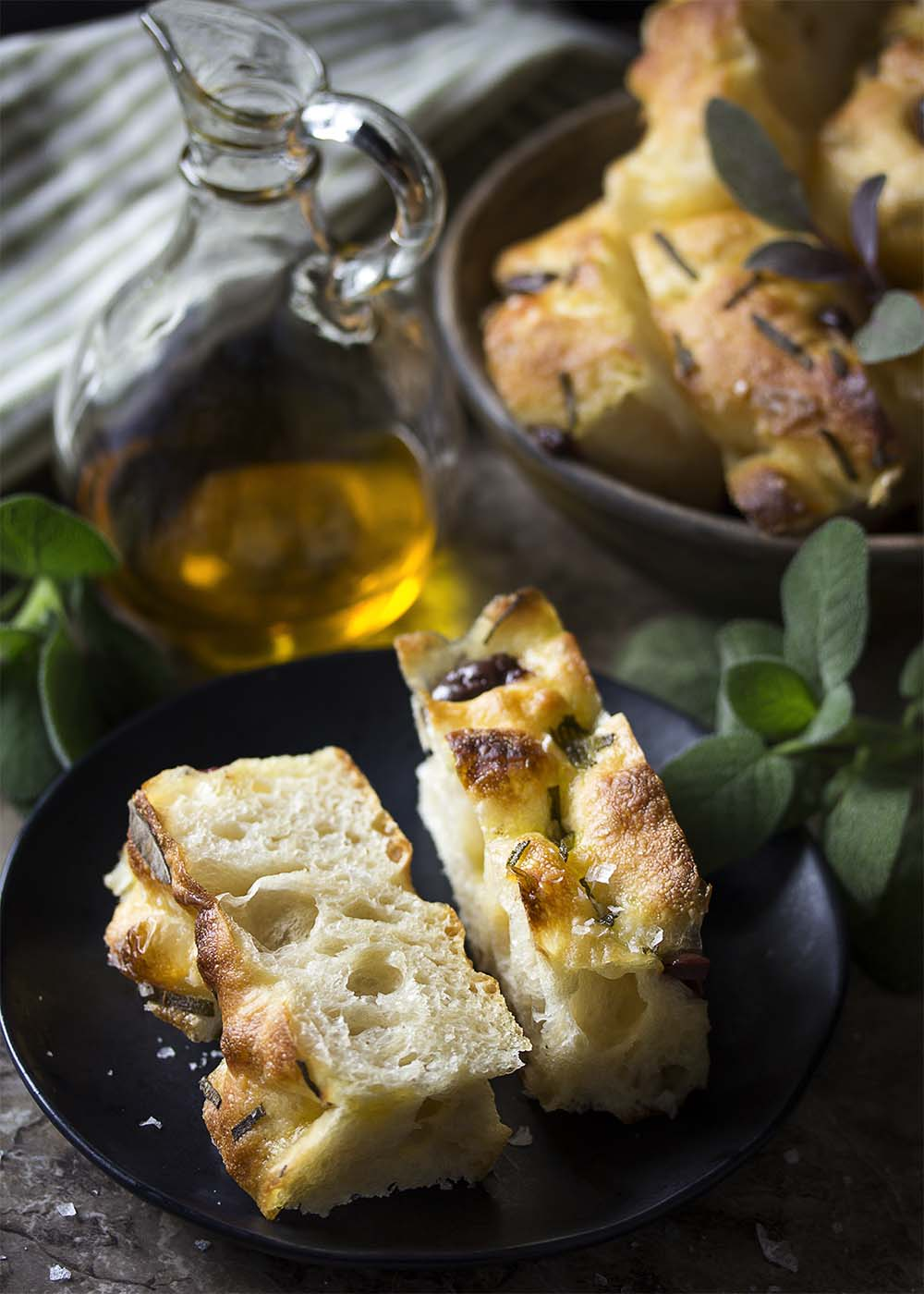 Two slices of soft and chewy olive focaccia on a plate with more slices in the background and olive oil for dipping in a cruet.