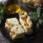 No-knead bread is so easy to make! Just stir everything together, let it rise, and bake. This recipe for sage and olive focaccia is baked right in a cast iron skillet for a soft and chewy interior and crispy crust.   justalittlebitofbacon.com #breadrecipes #focaccia #italianrecipe #castiron #nokneadbread