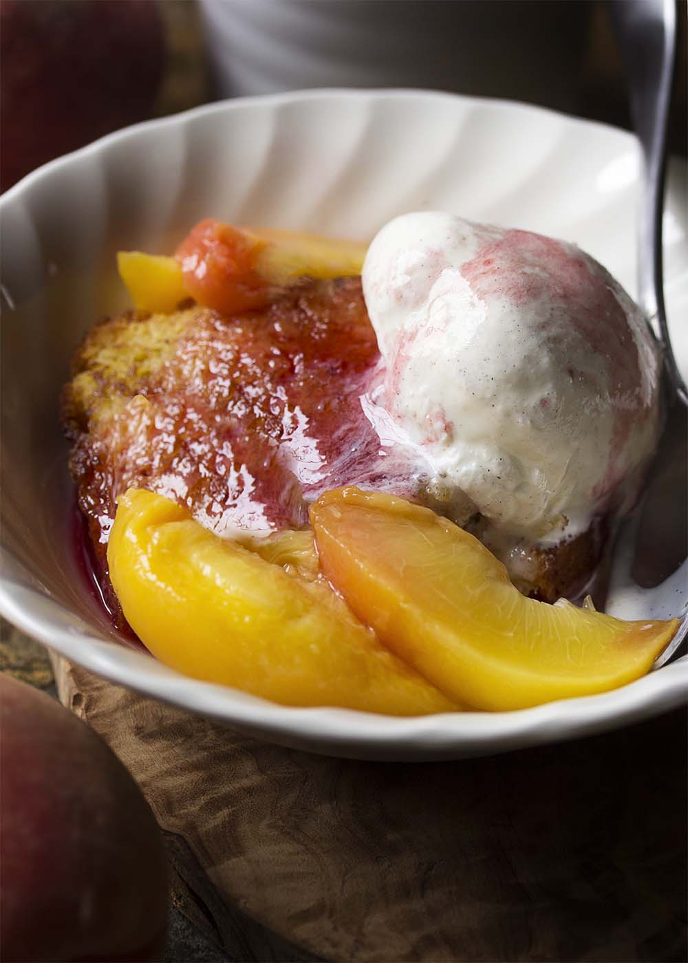 Close up of a bowl of toasted pound cake topped with juicy poached peaches, spiced syrup, and melting vanilla ice cream.