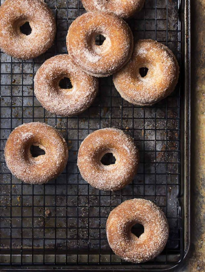 Skip the mess of deep frying and make baked cider donuts instead! These easy fall treats coated in cinnamon sugar are perfect dunked into apple cider for a morning snack or for dessert.   justalittlebitofbacon.com #donuts #doughnuts #applecider #fallrecipes #applerecipes #bakeddonuts
