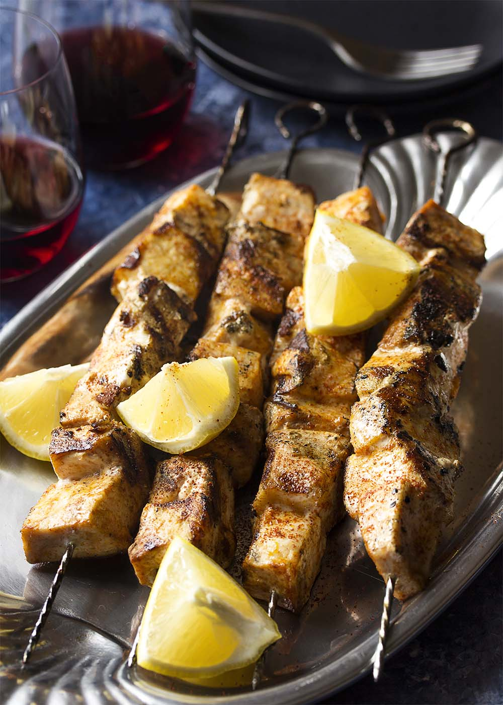 Spanish swordfish kebabs on skewers in a serving plate along with wedges of lemon.