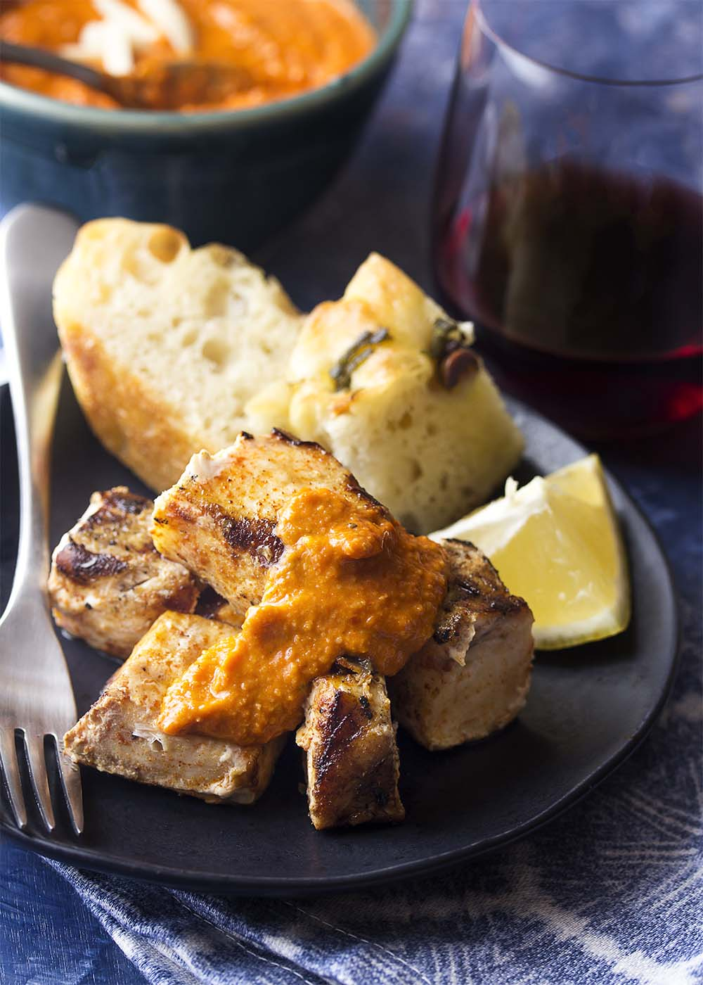 Juicy grilled cubes of swordfish piled on a plate and topped romesco sauce.