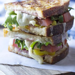 This spicy Italian panini is everything you love about Italian sub sandwiches in a toasted, melty, panini! Spicy peppers, gooey cheese, and yummy deli meats. Great for lunch or an easy dinner. | justalittlebitofbacon.com #panini #italianrecipes #sandwiches #italian