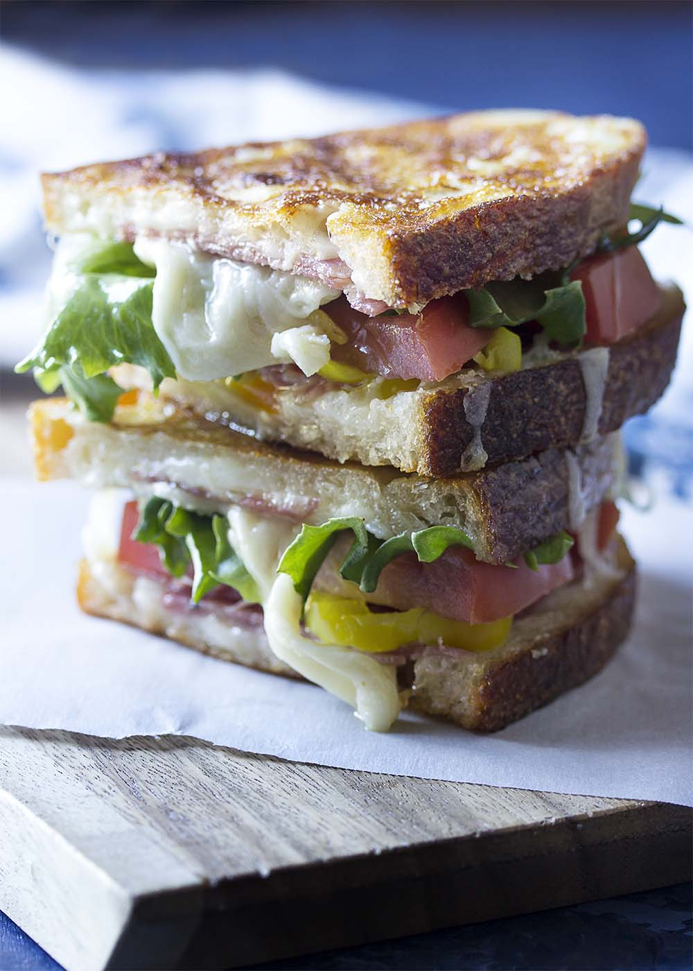 Close up of a golden brown panini full of Italian sub ingredients.