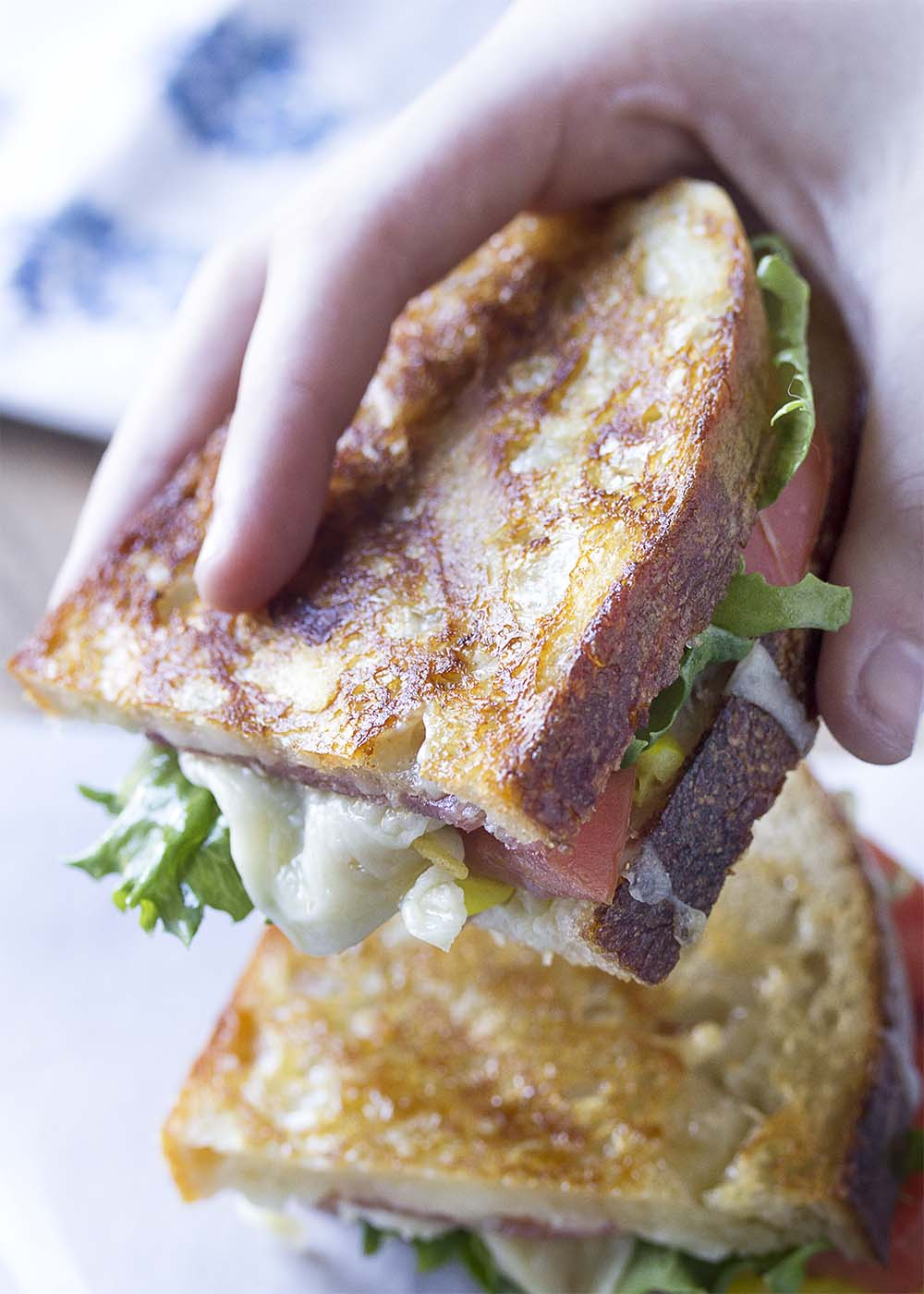 Hand lifting grilled sandwich with melted cheese and lettuce hanging over the edge.