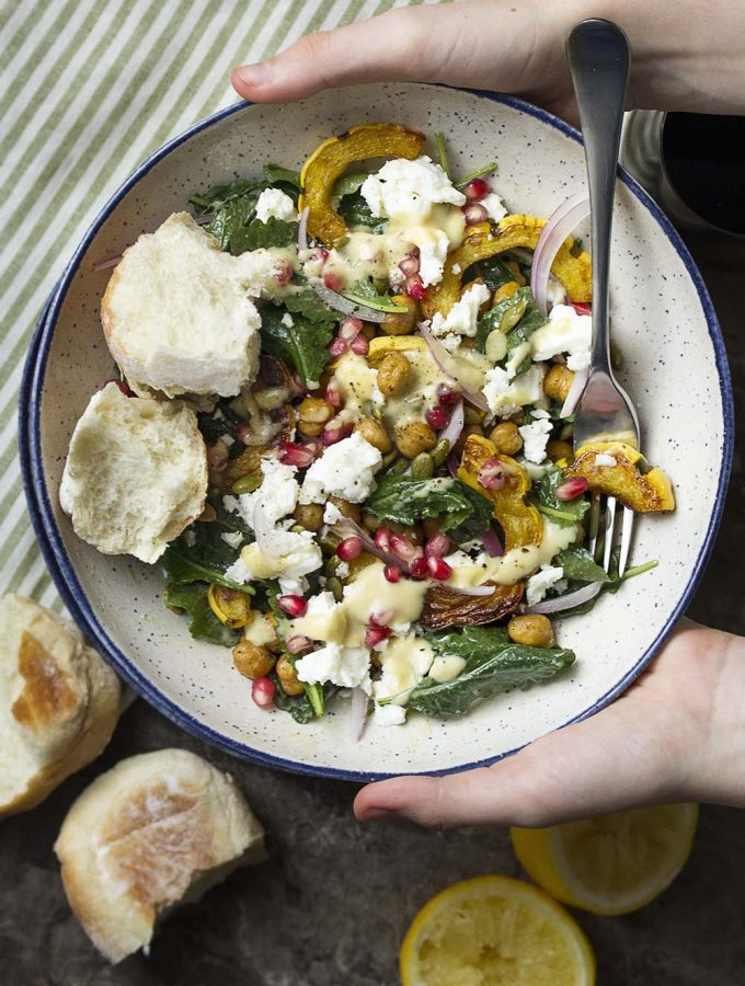 Roasted delicata squash salad is tossed with baby kale, roasted chickpeas, crumbled feta, and pomegranate and then drizzled with a creamy tahini dressing for a hearty and cozy fall vegetarian meal. Skip the feta for a vegan salad. Great as a side for Thanksgiving too! | justalittlebitofbacon.com #fallsalad #saladrecipe #vegetarianrecipe #delicatasquash #thanksgiving