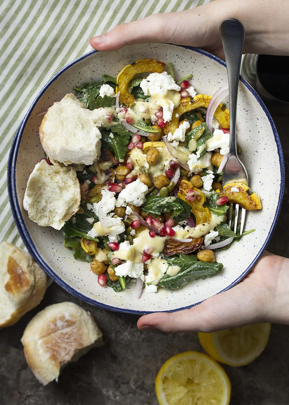 Hands holding up a bowl of roasted delicata squash salad with kale and chickpeas.