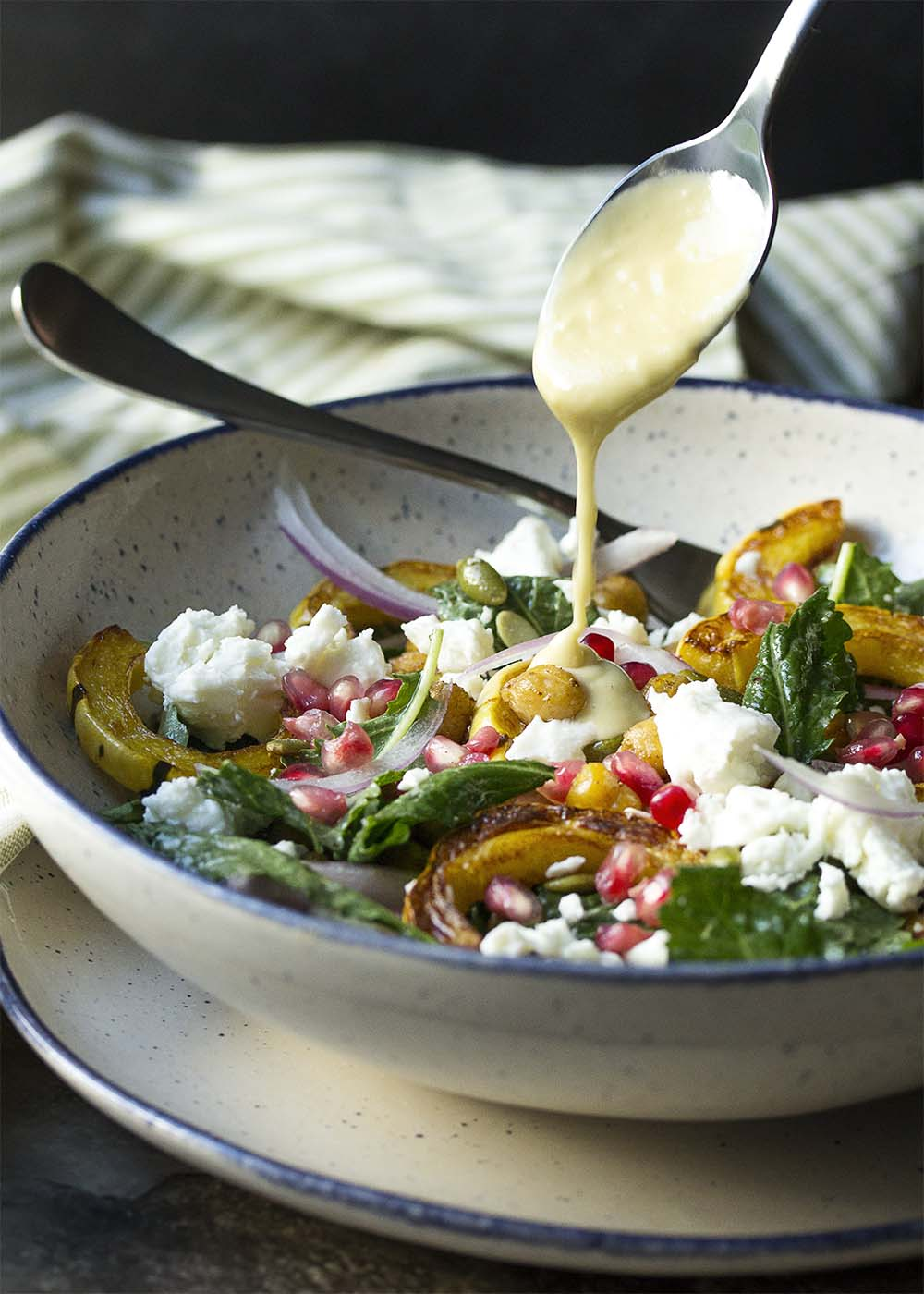 A spoon drizzling some creamy tahini dressing into the delicata squash salad.