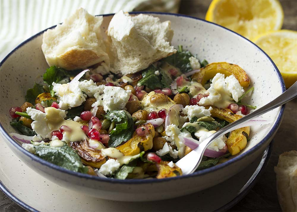 A fork digging into a bowl of squash and kale salad with chickpeas, pomegranate, feta, and pepitas.