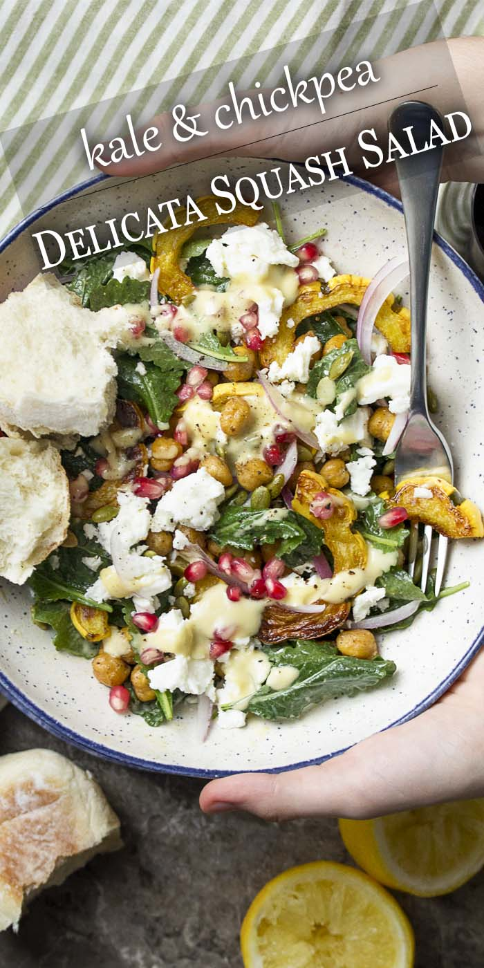 Hands holding a bowl of roasted squash, kale, and chickpeas with text overlay - Delicata Squash Salad.