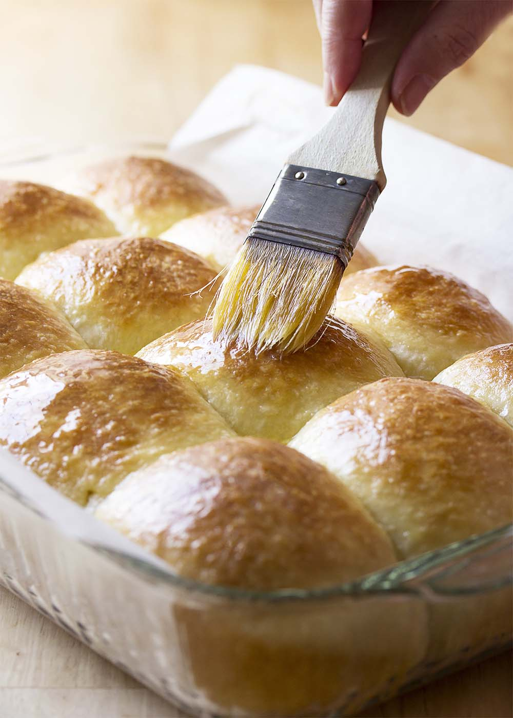 A pan of no-knead dinner rolls hot from the oven being brushed with melted butter.