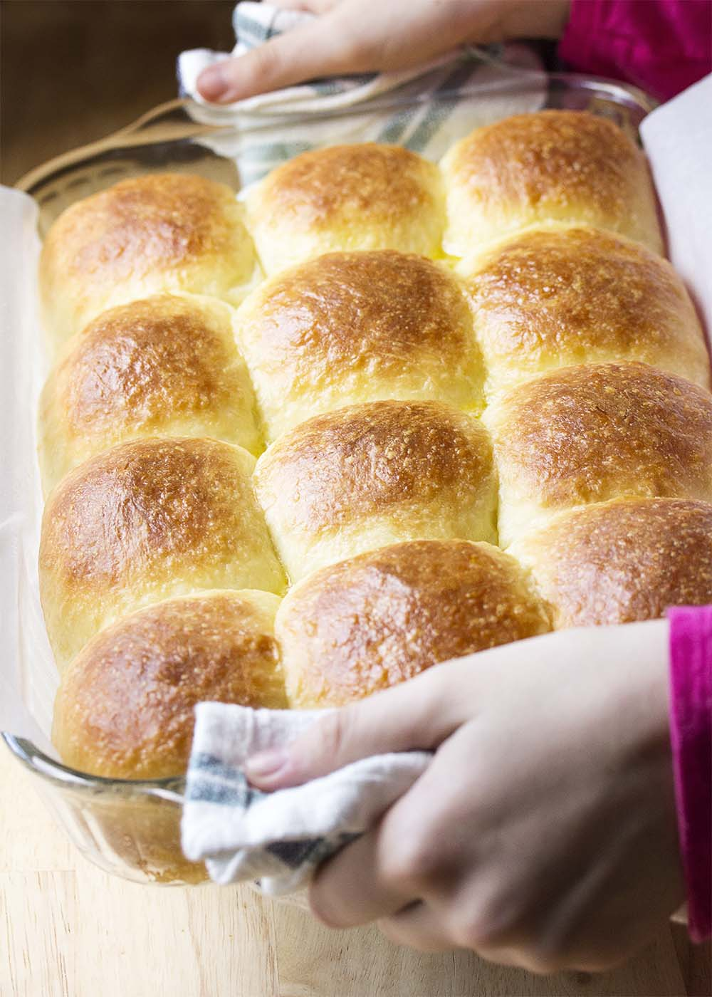 Hands holding up the baking pan of finished dinner rolls all glossy from being brushed with melted butter.