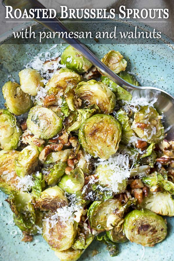 Close up of roasted sprouts in a serving bowl with text overlay - Roasted Brussels Sprouts.