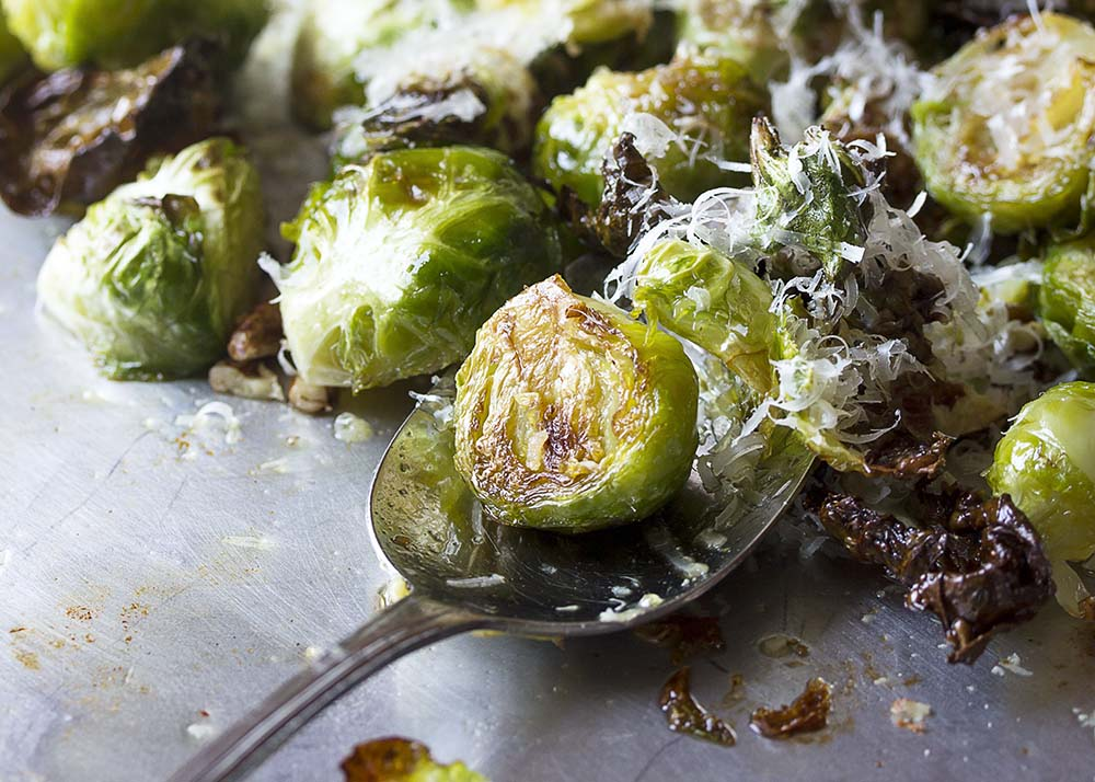Close up of roasted brussels sprouts in the baking pan showing the crispy edges.
