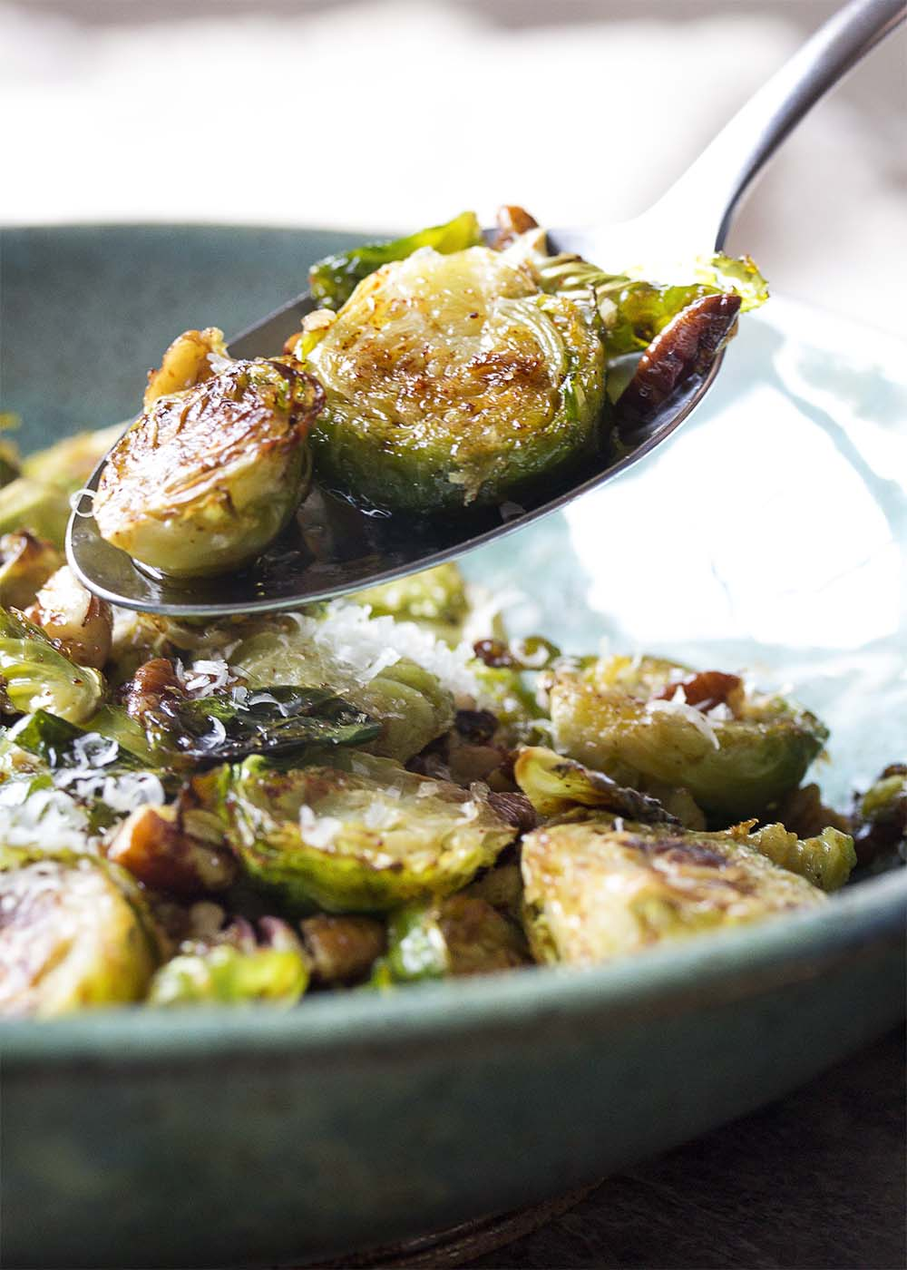 A spoonful of browned roasted brussels sprouts lifting out of the serving bowl.