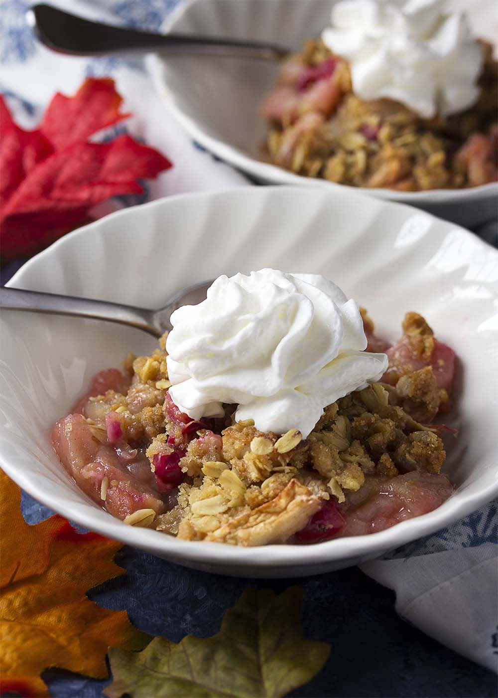 Bowls of warm apple cranberry crisp all topped with whipped cream, spoons in the bowls all ready to eat.