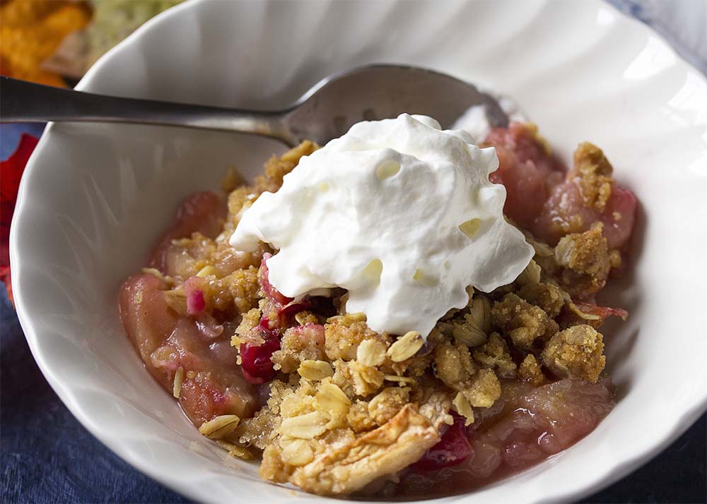Close up of a whipped cream topped bowl of apple cranberry crisp where you can see the soft apples, browned oats, the pink of the cranberries.