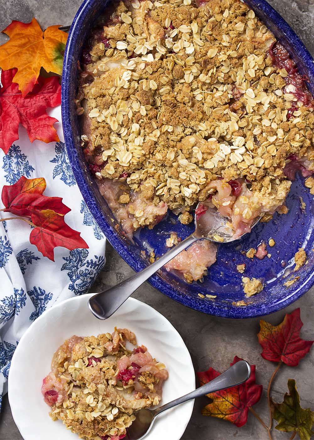 Top view of the baked apple cranberry crisp in a rustic blue oval baking dish with one bowl of crisp scooped out.