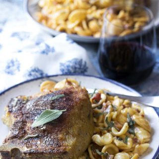 Pull out your cast iron skillet to make these amazing breaded cheese stuffed pork chops for two! Start these Italian style bone-in chops on the stove top then move to the oven and finish up by making a quick sauce to serve over pasta. | justalittlebitofbacon.com #porkchops #porkrecipes #italianrecipes #datenightrecipes #dinnerfortwo
