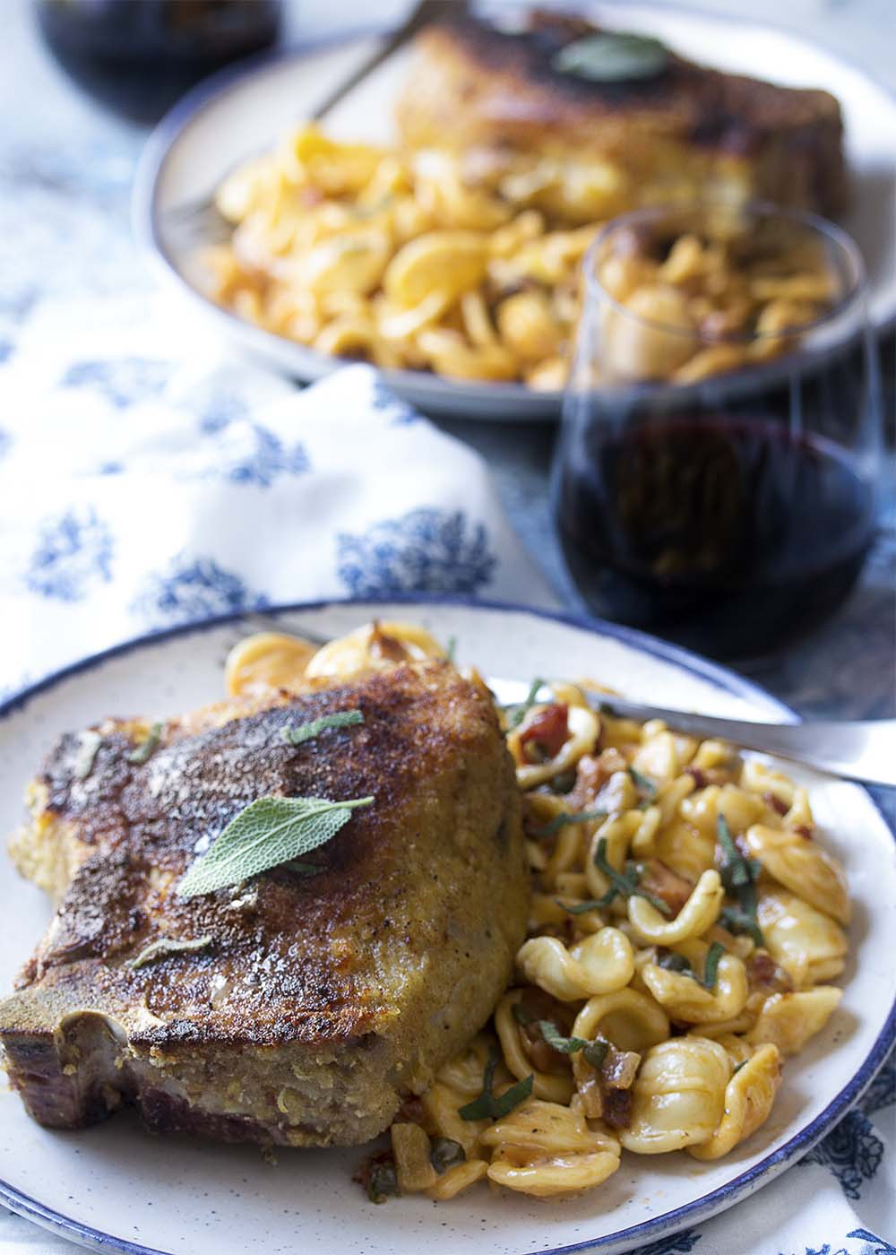 Two plates of breaded cheese stuffed pork chops over pasta.