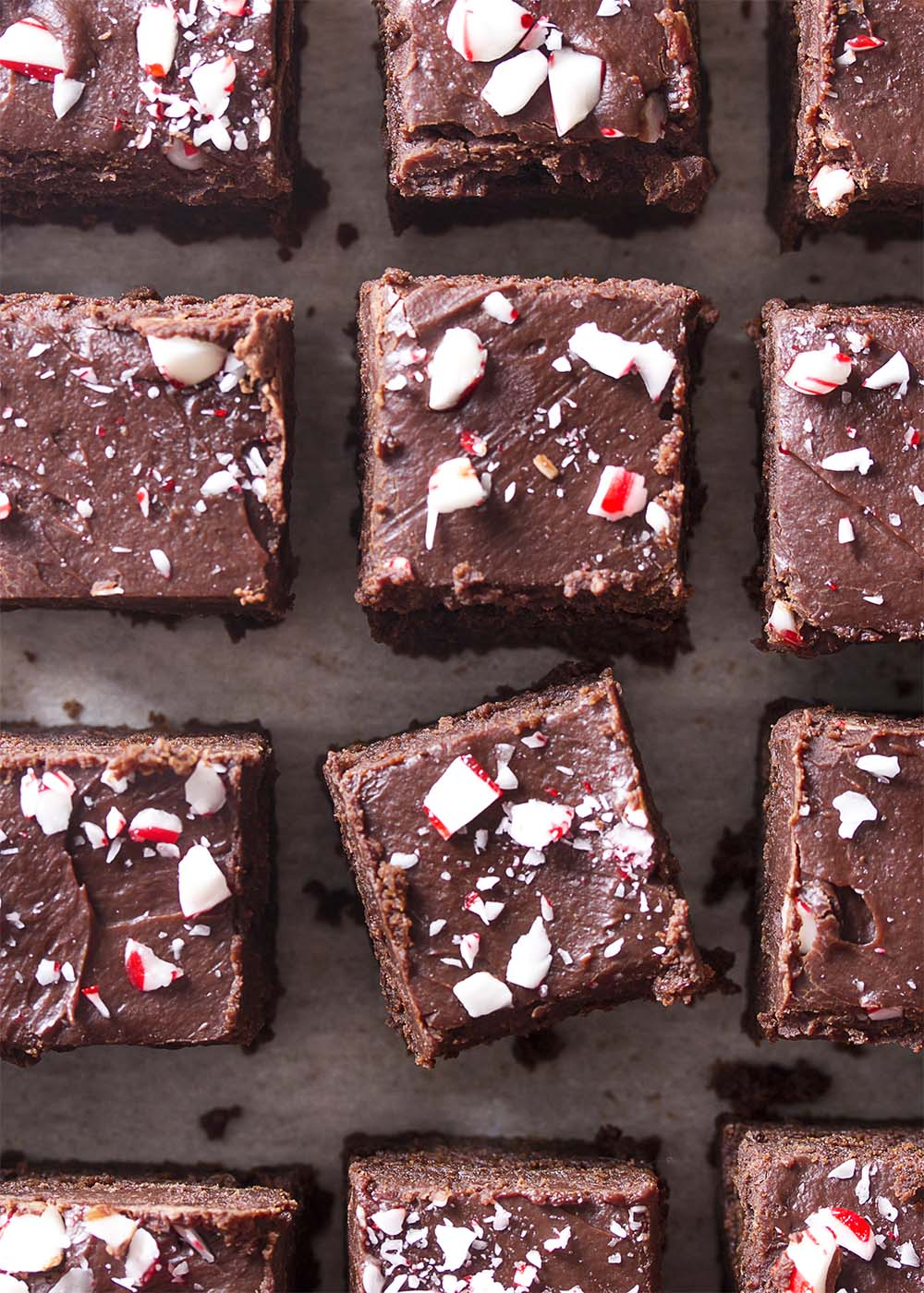 Top view of a grid of fudgy brownies sprinkled with crushed candy canes.