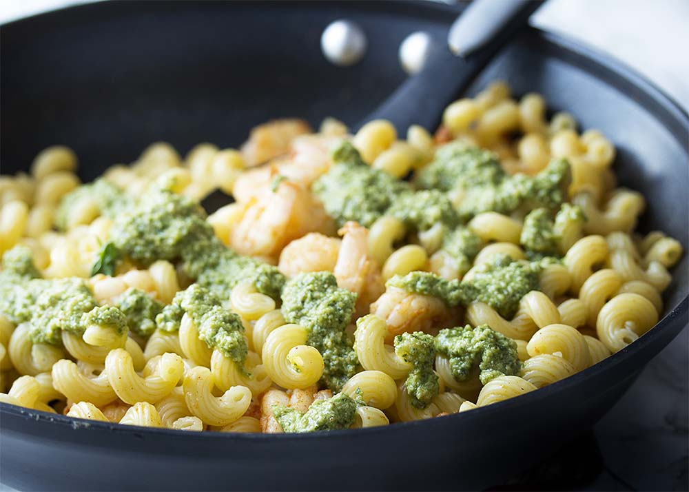 Pesto over pasta and shrimp in a skillet.