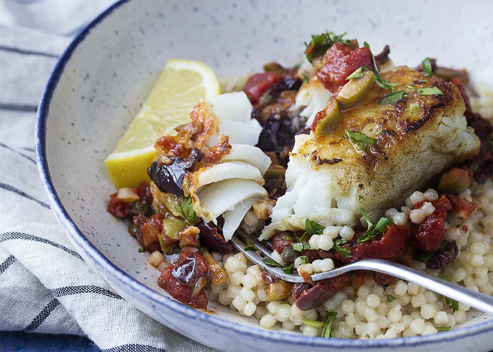 Close up a piece of perfectly cooked flaky cod topped with tomatoes and olives.