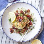For an easy and healthy weeknight dinner you'll love crispy pan seared cod with tomatoes, olives, and capers in a white wine and lemon sauce. | justalittlebitofbacon.com #italianrecipes #dinnerrecipes #fishrecipes #mediterraneandiet #codrecipes #italianfood