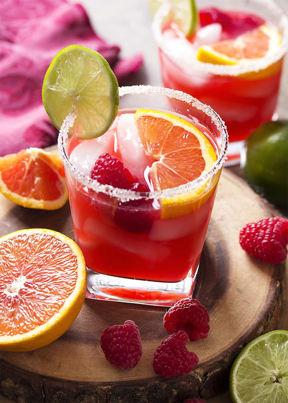Two raspberry orange margaritas each garnished with fruit and in sugar rimmed glasses.