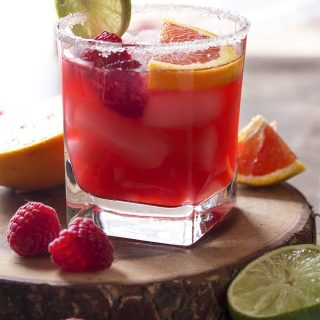 For an easy summer cocktail, try a raspberry orange margarita! Limes, orange juice, raspberry syrup, and triple sec on the rocks. Great for Cinco de Mayo or as a Valentine's drink! | justalittlebitofbacon.com #summerrecipes #cocktails #drinks #margaritas #valentines #cincodemayo