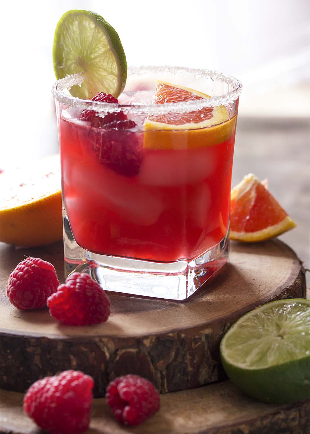 A margarita garnished with lime, orange, and raspberries in a sugar rimmed glass.