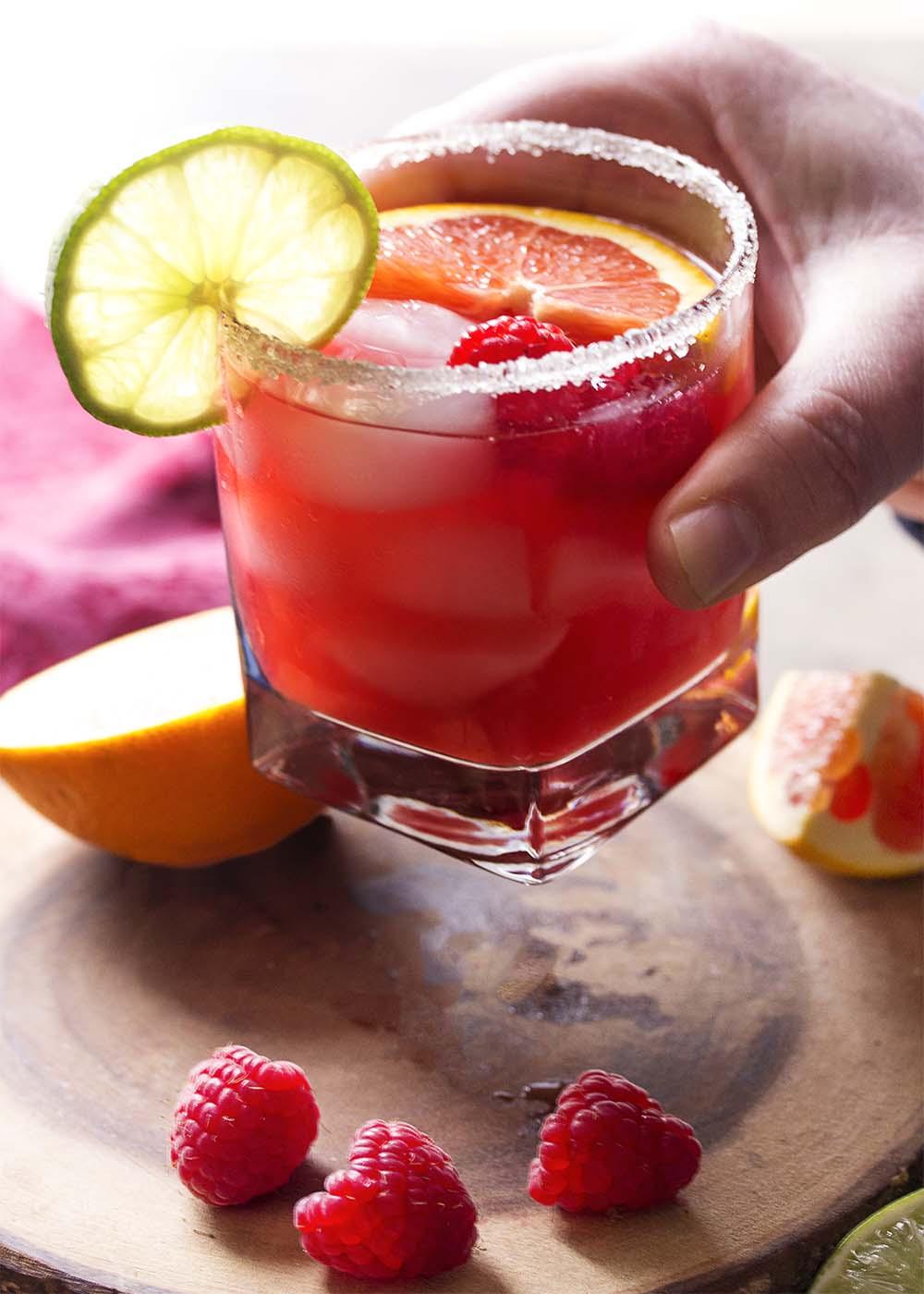 Hand lifting a glass of deep pink margarita.