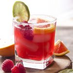 For an easy summer cocktail, try a raspberry orange margarita! Limes, orange juice, raspberry syrup, and triple sec on the rocks. Great for Cinco de Mayo, as for Valentine's, or as an anytime drink! | justalittlebitofbacon.com #summerrecipes #cocktails #drinks #margaritas #valentines #cincodemayo
