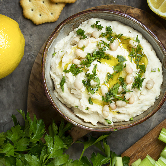 Fast and flavorful! This Italian-style Tuscan white bean dip is full of fresh thyme, garlic, and lemon zest and uses canned beans to make an easy and healthy party dip.   justalittlebitofbacon.com #veganrecipe #glutenfreerecipe #beandip #appetizers #dips #holidayrecipe #italianrecipe