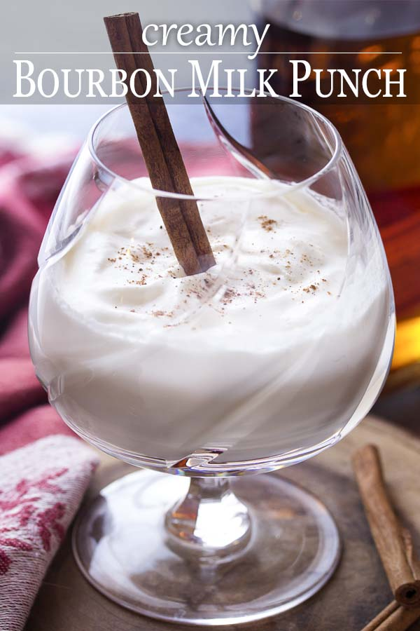 Hot milk cocktail in a glass with text overlay - Bourbon Milk Punch.