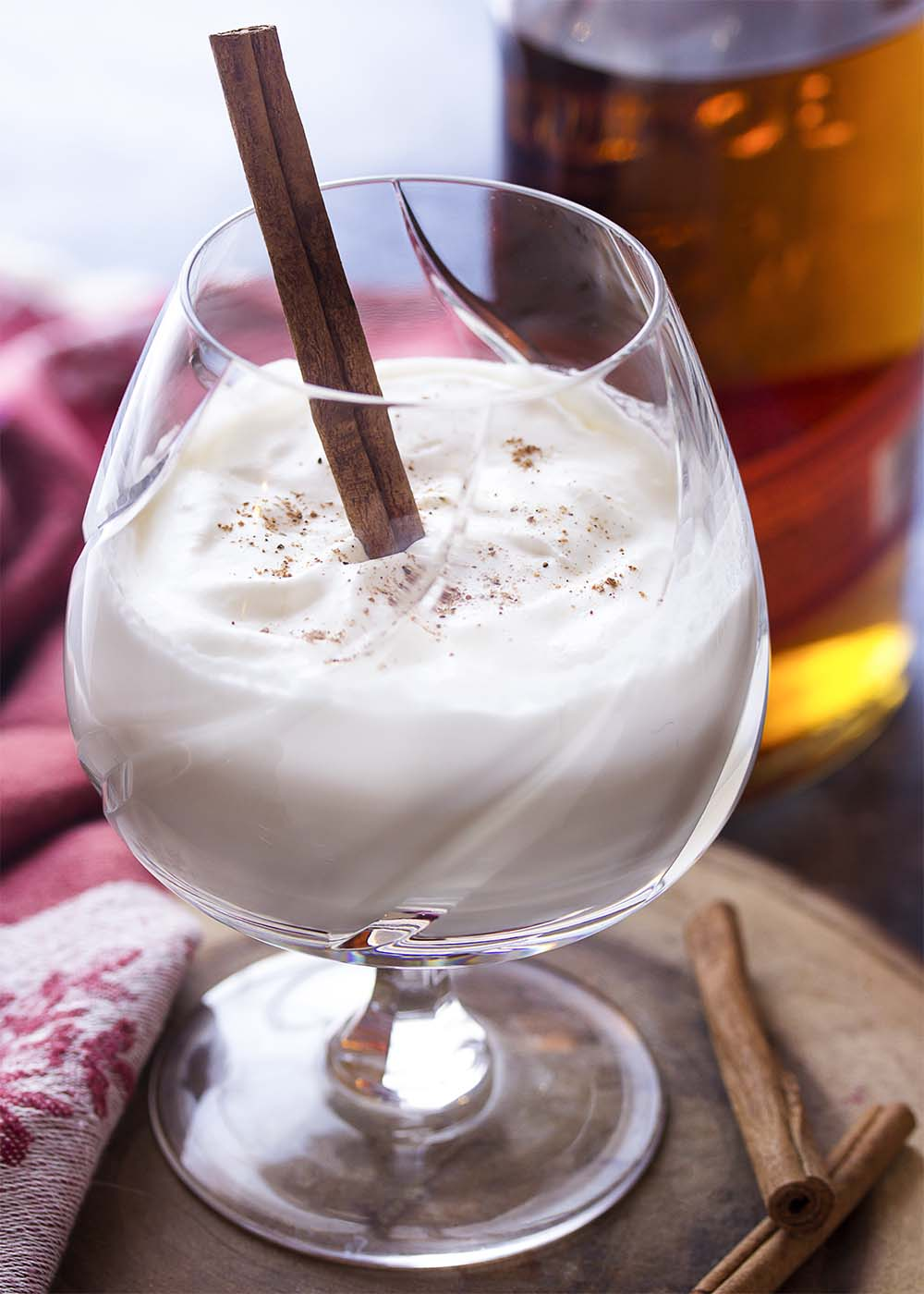 A snifter of spiced bourbon milk punch topped with whipped cream and nutmeg.