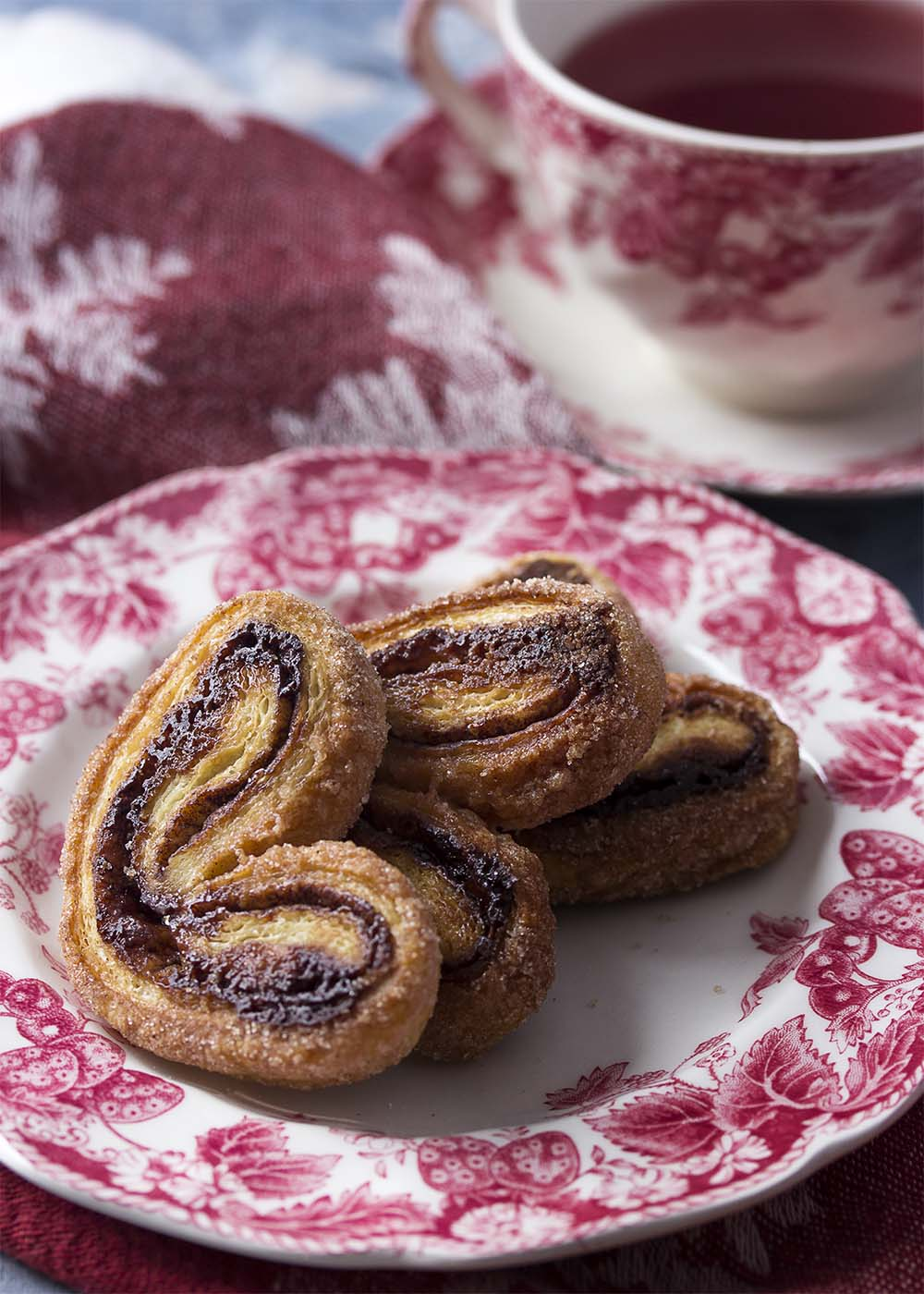 Cinnamon cocoa palmiers arranged on a plate with a cup of tea in the background.