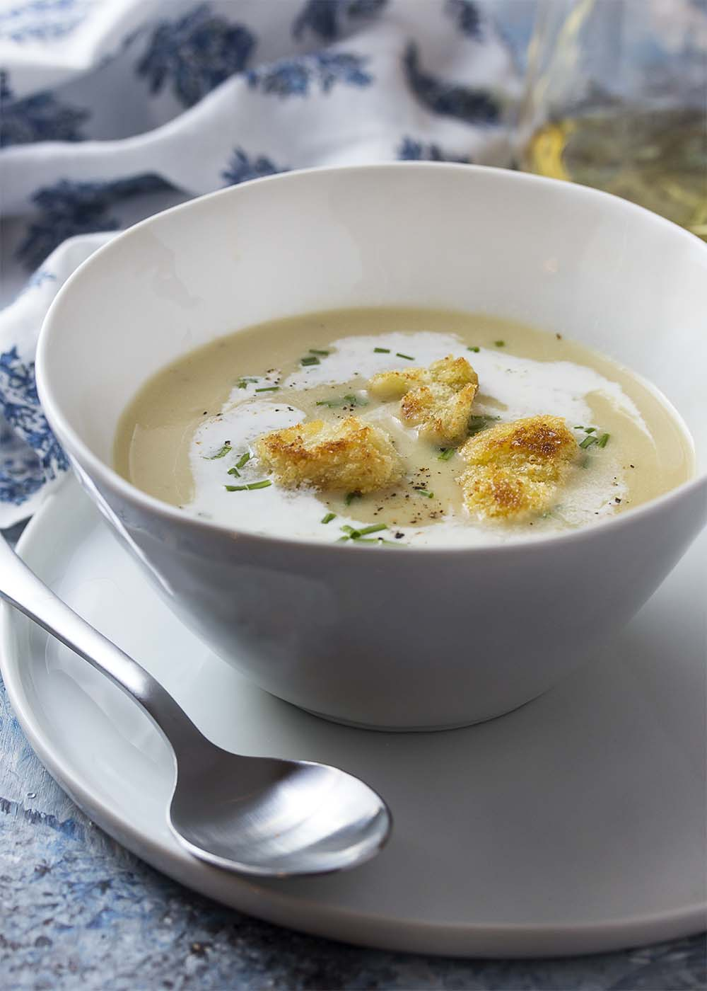 Close up of a white bowl of potato leek soup with crispy croutons garnishing the top.