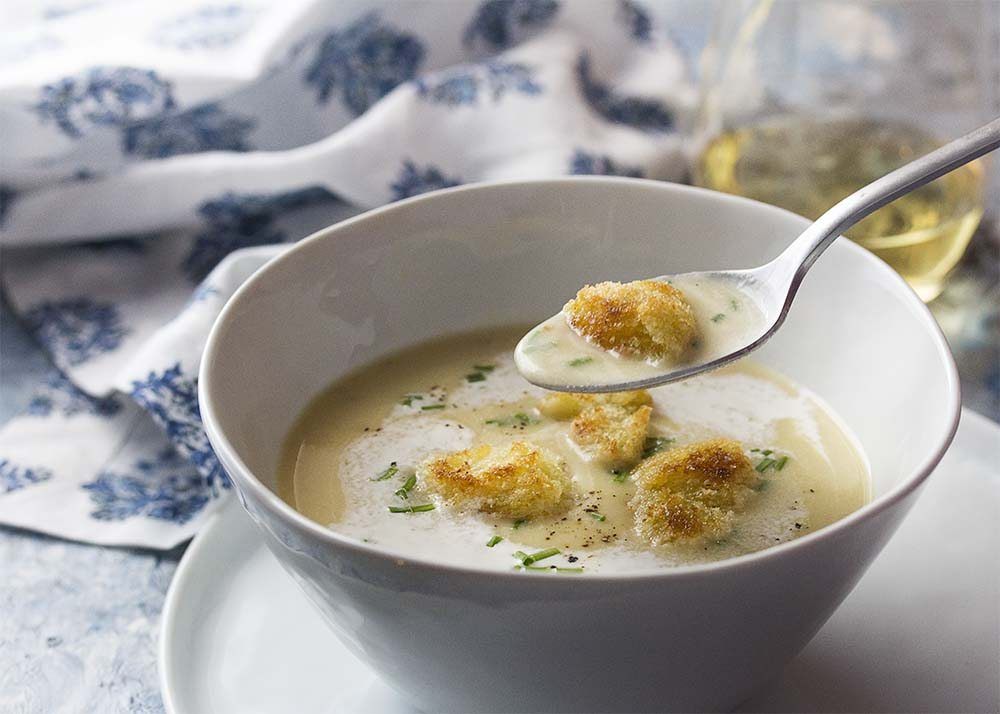 Taking a spoonful of creamy soup and croutons from a white bowl.