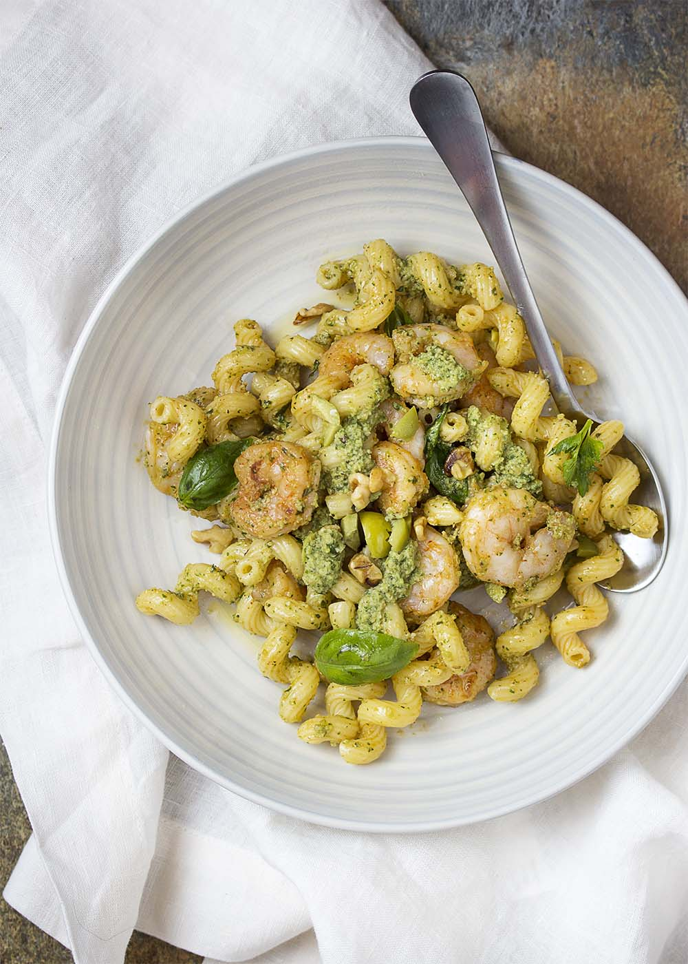 Top view of a bowl of pasta and shrimp, topped with basil leaves and walnuts.