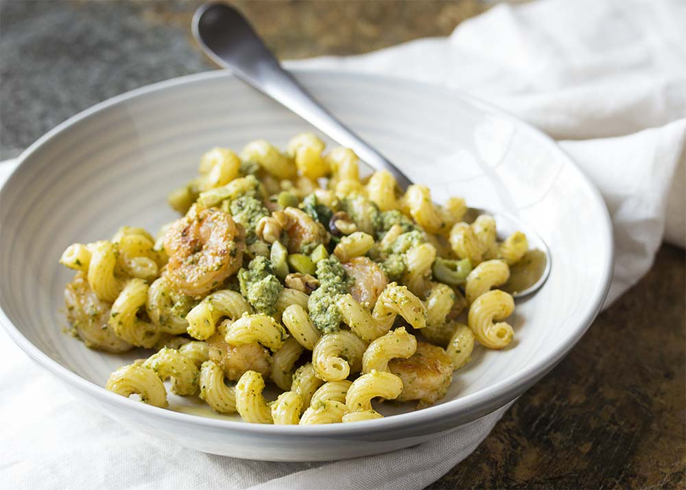 Close up of shrimp and pesto pasta in a bowl with a spoon.