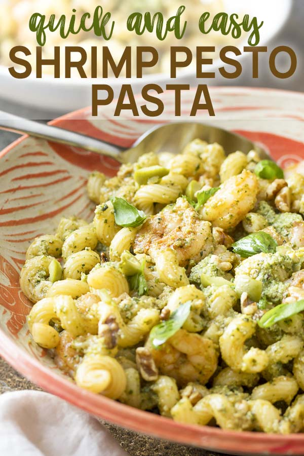 Pasta in a wide bowl tossed with herbs and shrimp with text overlay - Shrimp Pesto Pasta.