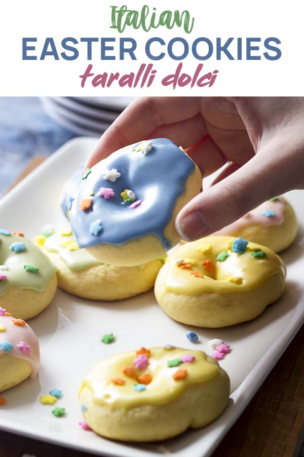 Cooling rack of colorful cookies and a hand holding on up with text overlay - Italian Easter Cookies.