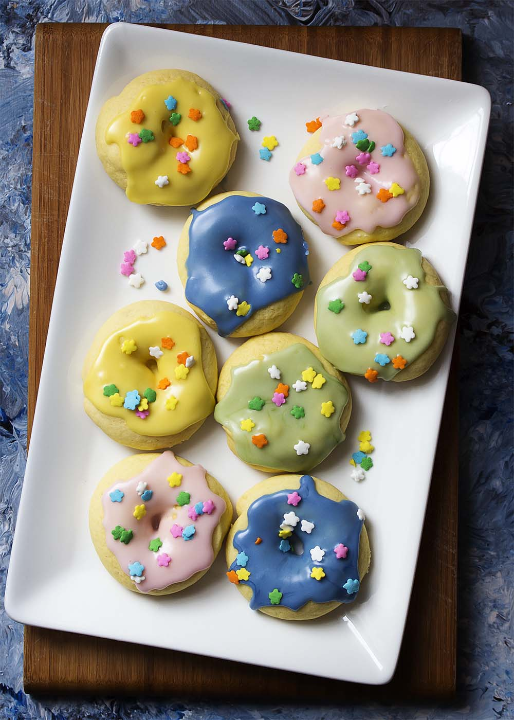 Top view of a platter of several colorfully glazed ring cookies topped with sprinkles.