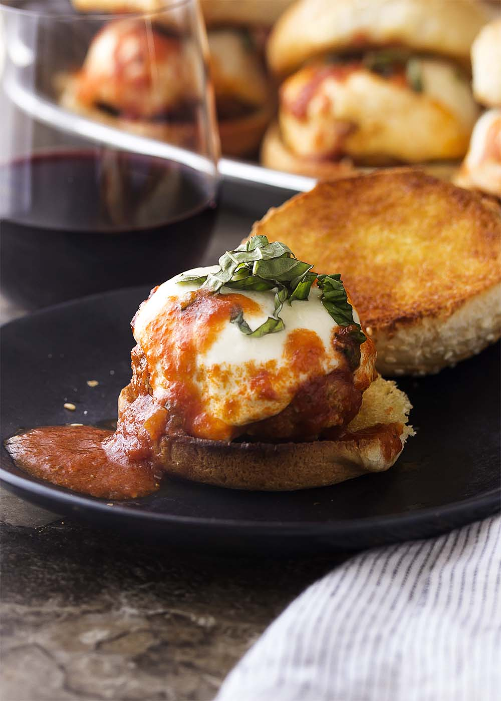 Italian meatball slider topped with melted mozzarella cheese and sliced basil on a toasted bun with marinara sauce. Glass of wine and more sliders in the background.
