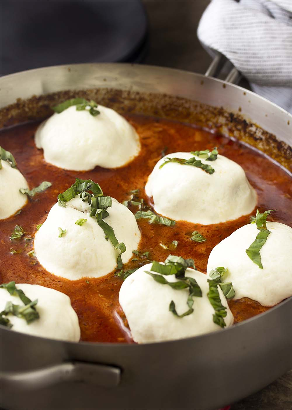 Italian meatballs in a skillet of marinara sauce topped with melted mozzarella and sliced basil.