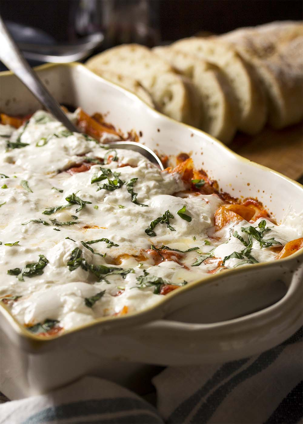 Casserole dish of vegetarian baked penne topped with melted buratta and sliced basil.