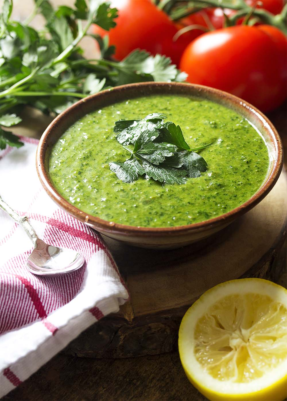 A bowl of green Italian herb sauce arranged with parsley and lemon.