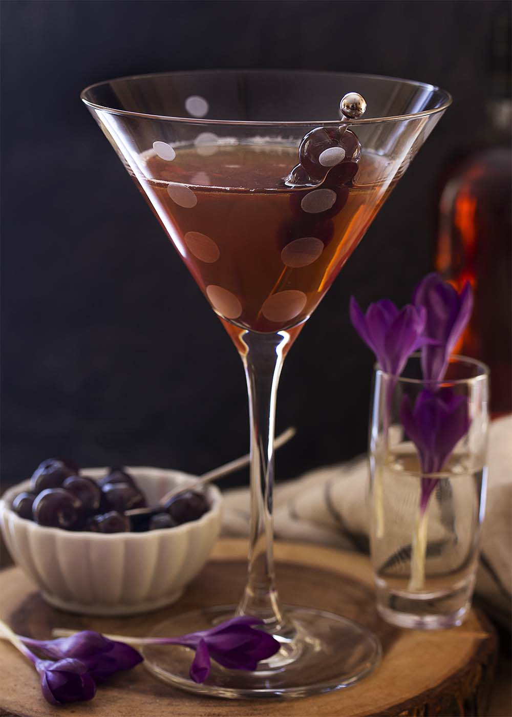 A tall martini glass containing a classic Manhattan cocktail garnished with three Amarena cherries.